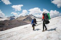 两个游人、一个男人和一名妇女有背包和起重吊钩的在他们的脚沿冰川走反对背景 图库摄影