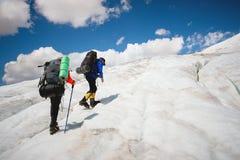 两个游人、一个男人和一名妇女有背包和起重吊钩的在他们的脚沿冰川走反对背景 免版税库存照片