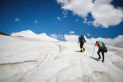 两个游人、一个男人和一名妇女有背包和起重吊钩的在他们的脚沿冰川走反对背景 免版税库存图片