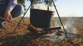 两个游人啤酒由远足在自然野营的剪影阳光日落的生活方式篝火坐特写镜头党 股票录像