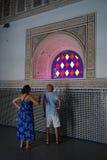 两个游人在El巴伊亚宫殿敬佩色的窗口在马拉喀什 库存图片