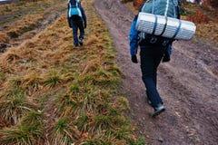 两个游人背面图有旅行的挑运上升在moun 库存照片