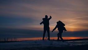 两个游人跑在日落跳的剪影滑稽的正面自然风景冬天雪 两位男性摄影师 股票视频