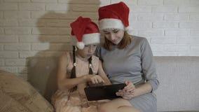 两个滑稽的姐妹、女孩和少年,在片剂的戏剧 他们并且笑坐在圣诞老人的帽子的沙发  股票视频