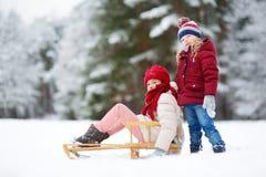 两个滑稽的小女孩获得与技巧的乐趣在美丽的冬天公园 使用在雪的逗人喜爱的孩子 免版税图库摄影
