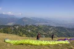 两个滑翔伞降伞为在山坡的起飞做准备反对城市的背景a的 免版税库存图片