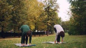 两个漂亮的女人在实践asanas和呼吸新鲜空气的席子的公园做着瑜伽 单独实践 影视素材