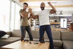 两个激动的男性朋友庆祝在电视上的观看的体育 库存图片