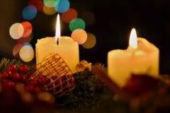 两个灼烧的蜡烛细节有背景在圣诞树安置的由五颜六色的bokeh光做成 库存照片