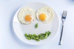 两个煎蛋用在白色板材,在轻的背景的叉子的青豆 库存图片