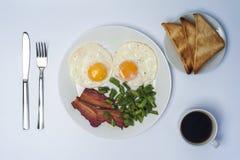 两个煎蛋用青豆和烟肉在白色板材、刀子、叉子、多士和咖啡在轻的背景 库存图片