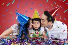 两个父母亲吻他们的生日聚会的孩子 库存照片