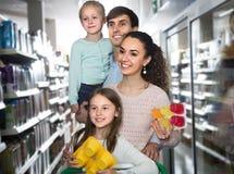 两个父母和两个孩子家庭在大型超级市场 图库摄影