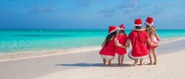 两个父母和孩子在圣诞老人帽子在白色海滩 免版税库存照片