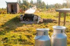 两个牛奶罐头和一个煮沸的水壶在一个老风景 免版税库存图片