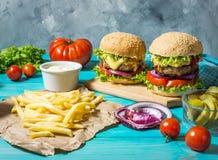 两个牛肉汉堡、油炸物土豆和黄瓜在蓝色木桌上 图库摄影