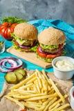 两个牛肉汉堡、油炸物土豆和黄瓜在蓝色木桌上 库存图片