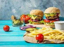 两个牛肉汉堡、油炸物土豆和黄瓜在蓝色木桌上 库存照片