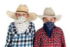 两个牛仔看照相机的兄弟戴帽子的和班丹纳花绸 免版税库存照片