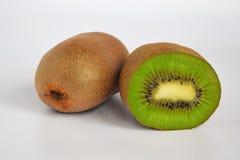 两个猕猴桃:一个是削皮的与棕色皮肤和其次是在白色背景的半,健康吃概念 库存图片