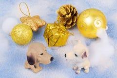 两个玩具狗在圣诞节装饰旁边坐 图库摄影