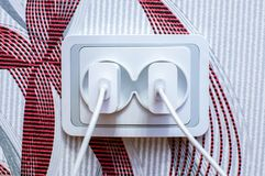 两个现代白细胞电话充电器塞住了入插口 能量废概念 免版税库存照片