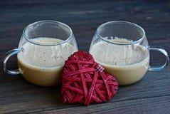 两个玻璃杯子用咖啡和红色心脏在桌上 免版税库存照片
