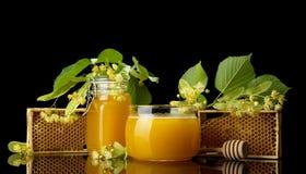 两个玻璃瓶子用在黑色和开花隔绝的菩提树蜂蜜 免版税库存图片