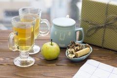 两个玻璃茶杯、苹果、糖罐、曲奇饼和礼物盒 免版税库存照片