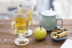 两个玻璃茶杯、苹果、糖罐和曲奇饼 免版税库存照片