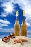 两个瓶与石灰的冰镇啤酒在一个美好的热带海滩设置 免版税图库摄影