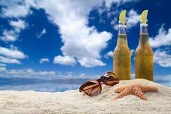 两个瓶与石灰的啤酒在海滩。 免版税库存图片