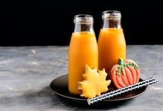 两个瓶南瓜汁用黑秸杆水平的照片万圣夜食物和甜点复制空间 免版税库存图片