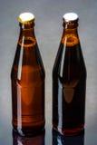 两个瓶反射性表面上的啤酒 免版税库存照片