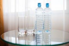 两个瓶和两块玻璃在桌上 免版税库存照片