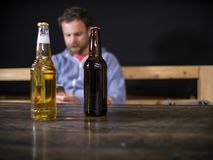 两个瓶啤酒在桌上站立以调查电话的一个坐的人为背景 库存照片