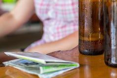 两个瓶在一个黑褐色瓶的啤酒有在一张木桌上的旅游地图的与在被弄脏的背景的拷贝空间 库存照片