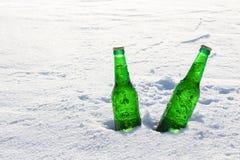 两个瓶在雪的冰镇啤酒在日落 库存照片