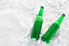 两个瓶在雪的冰镇啤酒 免版税库存图片