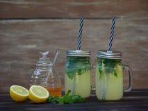 两个瓶子与闪耀的矿泉水、薄菏和蜂蜜的新鲜的柠檬水 库存图片