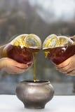 两个瓶子用蜂蜜、罐和四只妇女的手 免版税库存照片
