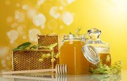 两个瓶子蜂蜜,菩提树开花,与蜂窝的木制框架在黄色背景 免版税库存图片