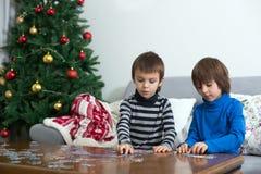 两个甜孩子,在家收集难题在圣诞节 库存照片