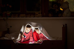 两个甜男孩,在床上读一本书在上床时间以后,使用闪光 免版税库存照片