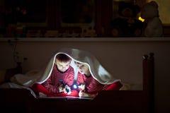 两个甜男孩,在床上读一本书在上床时间以后,使用闪光 免版税库存图片
