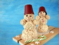 两个甜雪人由喘气的米制成在蓝色背景 免版税库存照片