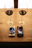 两个电话、圆环和两杯在桌上的酒 库存图片