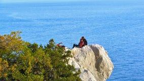 两个男人和基于岩石壁架的妇女在海上的 免版税库存图片