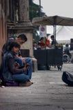 两个男孩使用和唱歌坐地面的街道执行者 库存照片