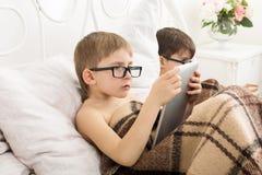 两个男孩使用在膝上型计算机和片剂有狗的在床上 免版税库存图片